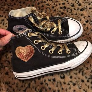 Black hightop Converse with gold accent patches